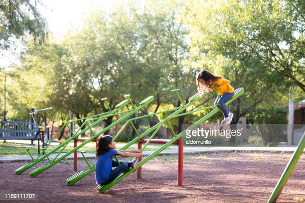 sisters playing on a seesaw together - biciancola foto e immagini stock