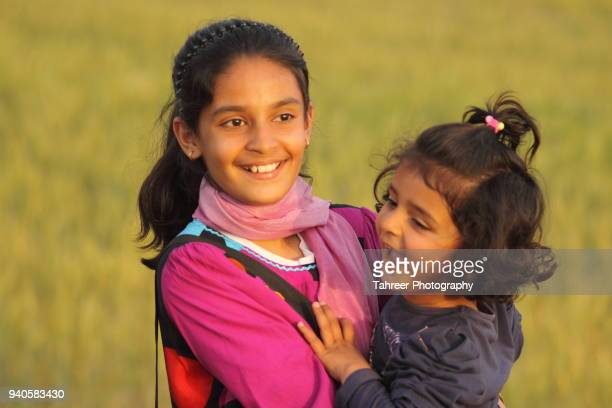 sisters playing - pakistan girl stock photos and pictures