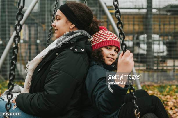 sisters playing together on nest swing seat - city life stock pictures, royalty-free photos & images