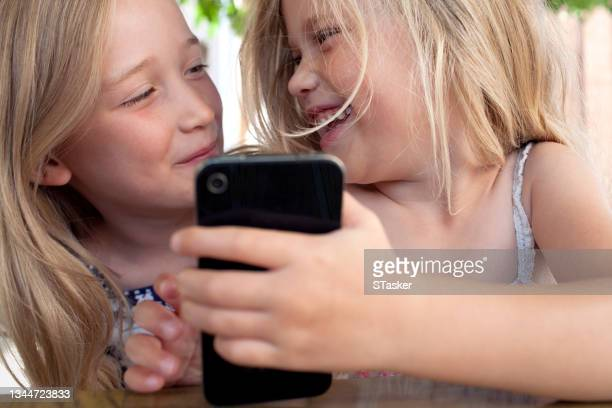 sisters playing with a phone - st. albans stock pictures, royalty-free photos & images