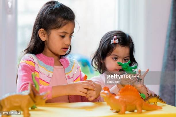 sisters playing with dinosaur toys - simple living stock pictures, royalty-free photos & images