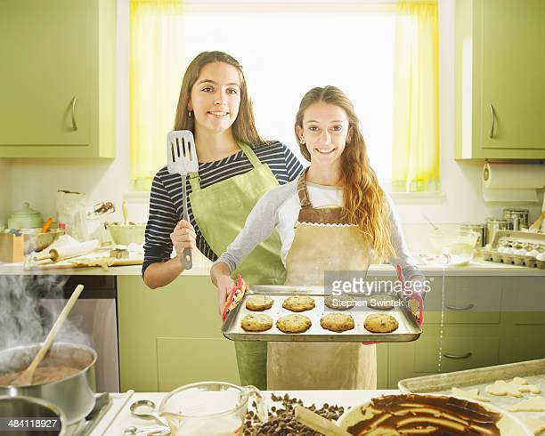 Sisters posing with a sheet of cookies