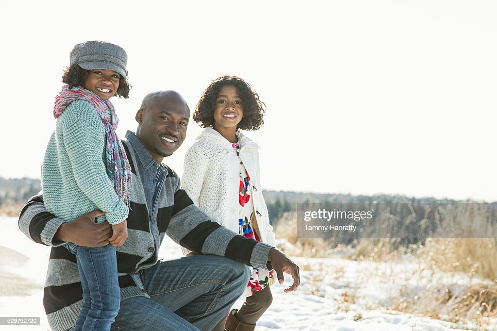 Sisters (8-9,10-12) posing with her father on snow : Foto de stock