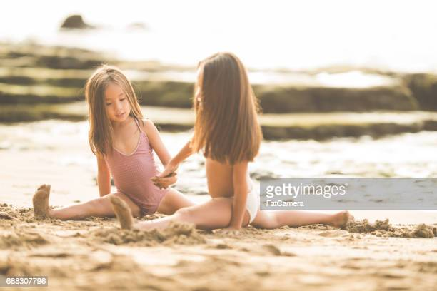 Sisters practicing gymnastics in the sand