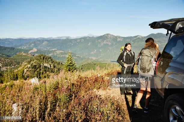 sisters preparing for backpacking trip at back of car on fall afternoon - 4x4 stock pictures, royalty-free photos & images