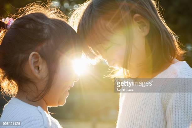 姉妹一緒に頭を置くとバックライトを浮かべて外 - 絆 ストックフォトと画像