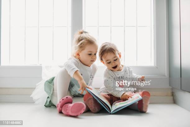 sisters reading a book together in a window seat - beautiful turkish girl stock pictures, royalty-free photos & images
