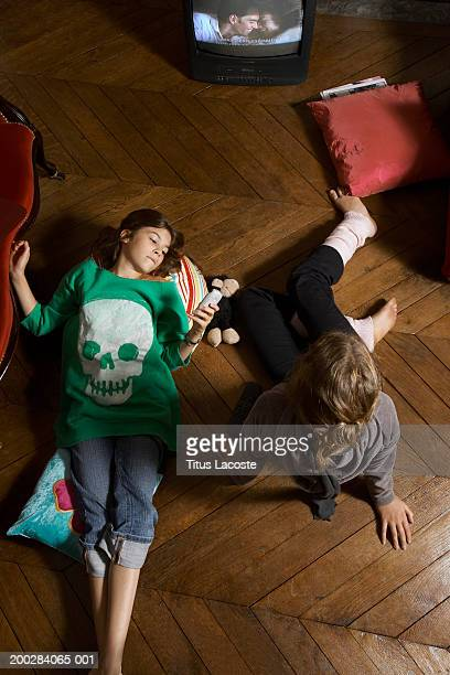 Sisters (11-13) relaxing on living room floor, one watching television