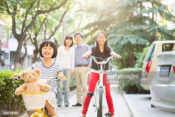 Sisters Ride Their Bicycles While Parents Watch