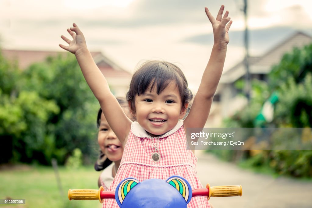 Sisters Riding Tricycle On Road At Public Park : Stock Photo