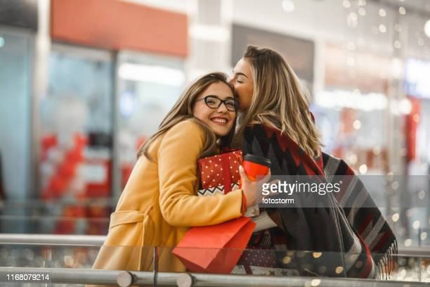 sisters sharing christmas presents - shopping centre stock pictures, royalty-free photos & images