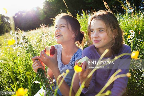 Sisters sitting in field eating apples