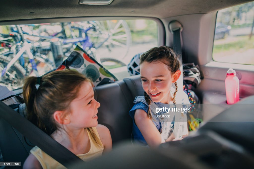Sisters Sitting in Their Family Car : Stock Photo