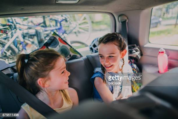 sisters sitting in their family car - family inside car stock photos and pictures