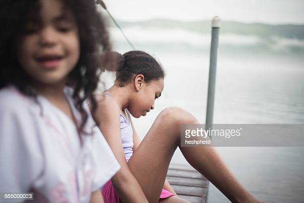 sisters sitting on dock on summer vacation at lake george, new york, usa - heshphoto fotografías e imágenes de stock