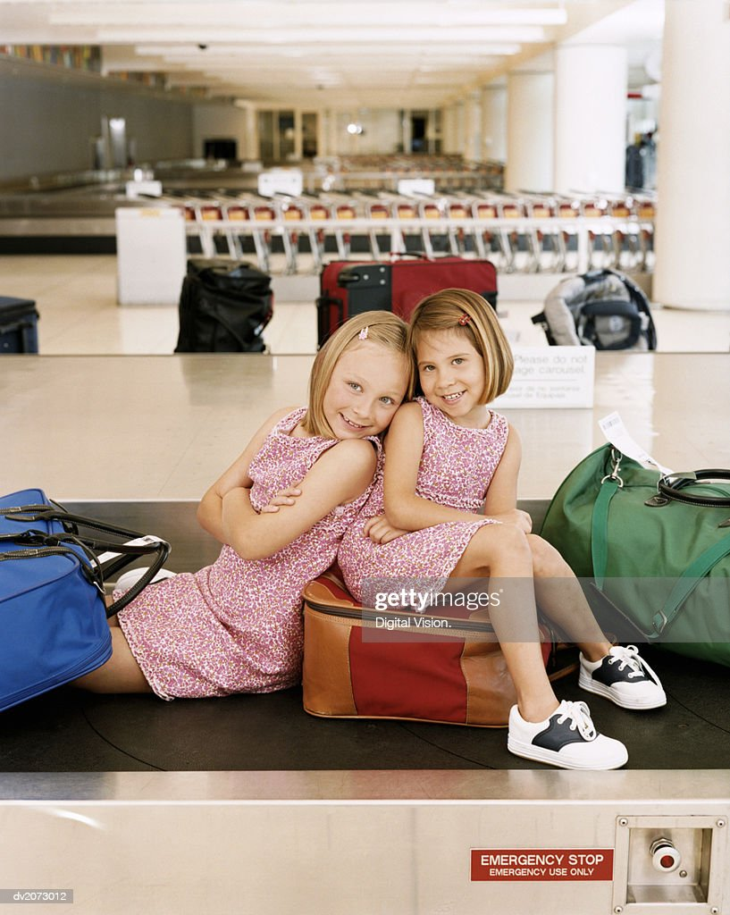 Sisters Sitting on Suitcases at Airport Baggage Collection : Stock Photo