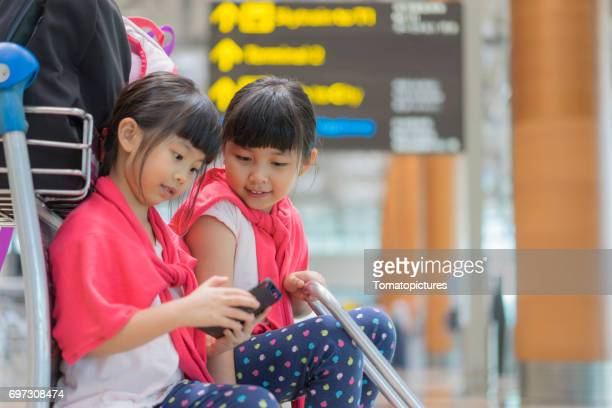 sisters sitting on suitcases in airport - asian twins stock photos and pictures
