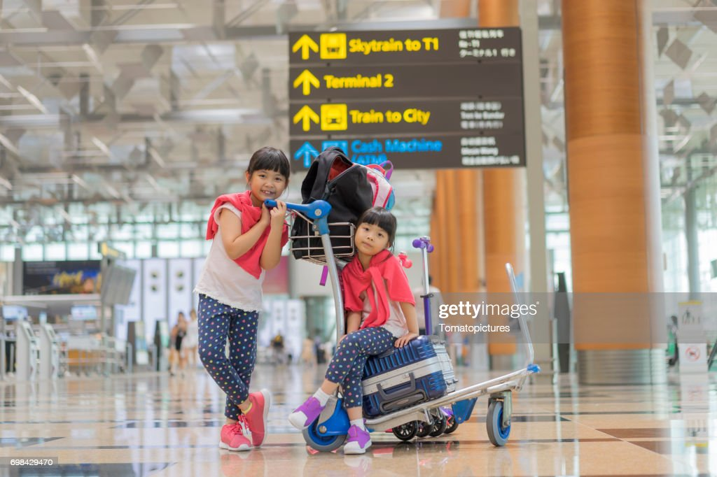 Sisters sitting on suitcases in airport : Stock Photo