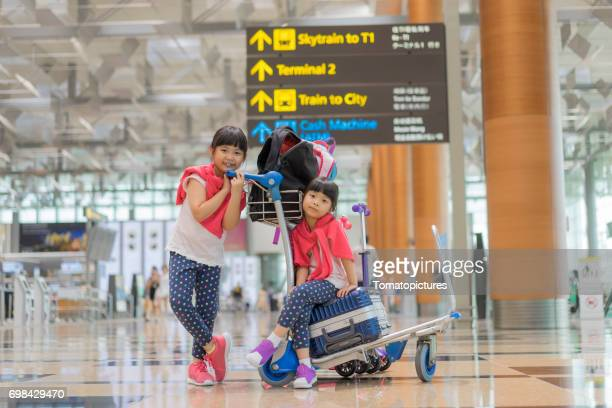 Sisters sitting on suitcases in airport