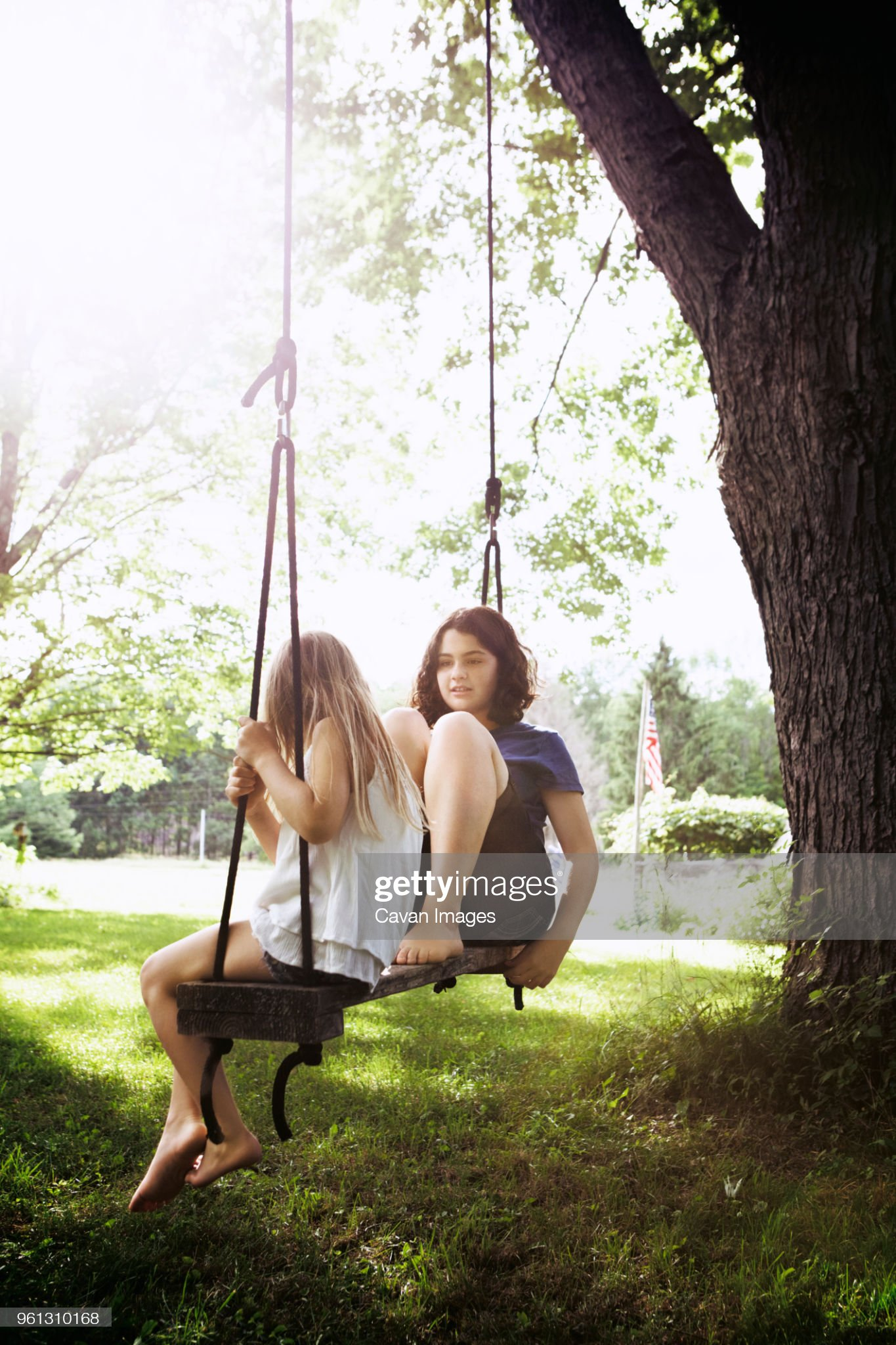 https://media.gettyimages.com/photos/sisters-sitting-on-swing-at-grass-field-picture-id961310168?s=2048x2048