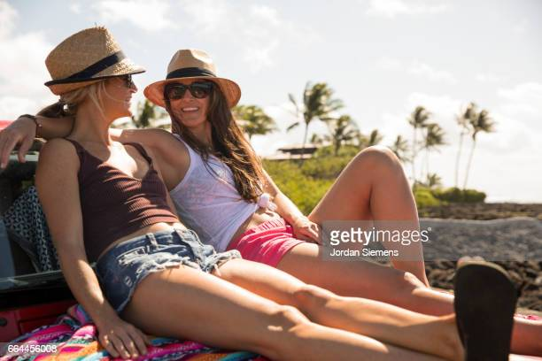 sisters sitting on the hood of their car. - only mid adult women stock pictures, royalty-free photos & images