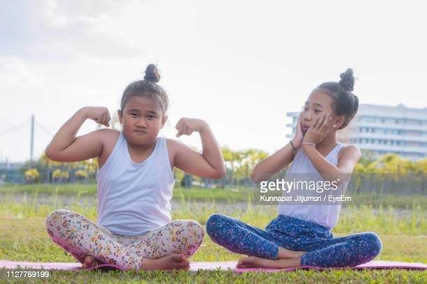 Sisters Sitting On Yoga Mat At Park
