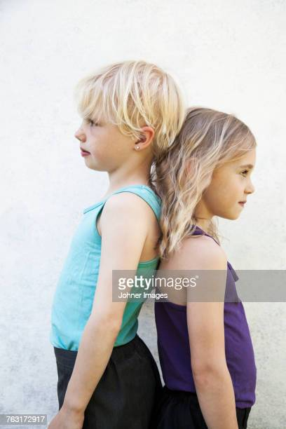 sisters standing back to back - gender inequality stock photos and pictures