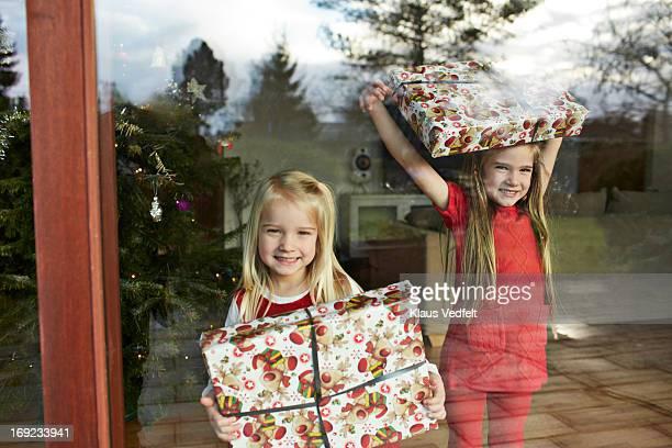 Sisters standing behind window w. presents