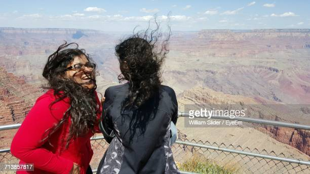 Sisters Standing By Railing At Grand Canyon National Park