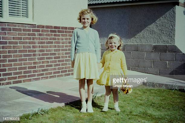 sisters standing in garden - sister stock photos and pictures