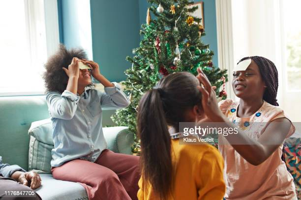 sisters sticking notes on forehead at home - tradition stock pictures, royalty-free photos & images