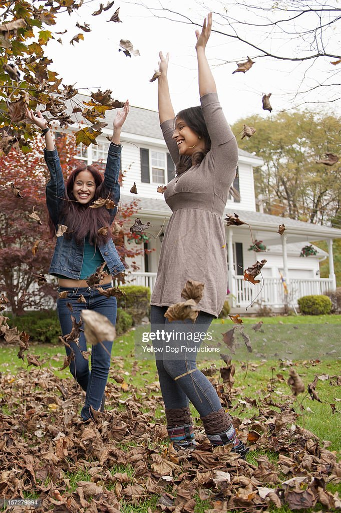 Sisters throwing autumn leaves in air : Stock Photo