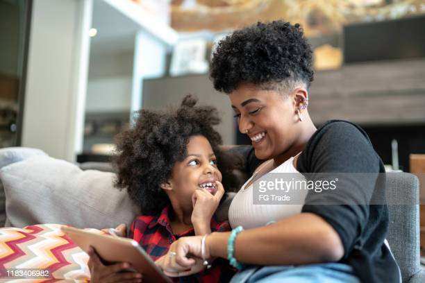 sisters using a digital tablet - family at home stock pictures, royalty-free photos & images