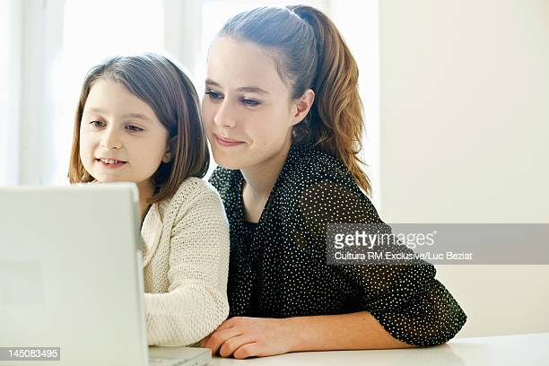 Sisters using laptop together