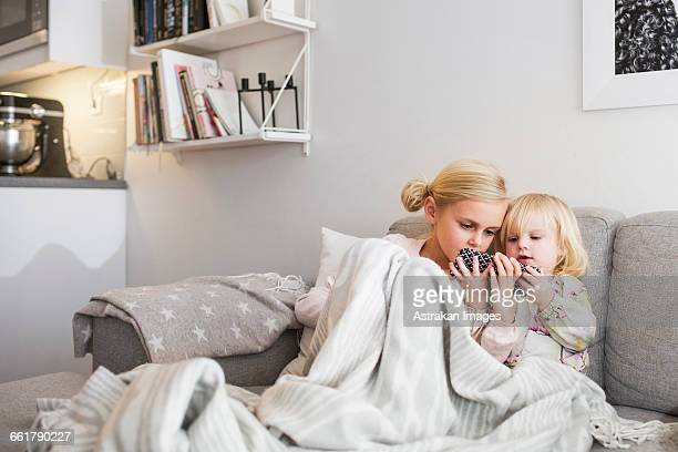 Sisters using mobile phone while relaxing on sofa at home