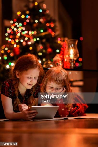 Sisters using tablet PC on floor during Christmas