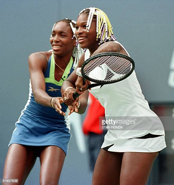 Sisters Venus and Serena Williams share a racket during an exhibition match 29 August at the US Tennis Center in Flushing Meadows New York prior to...
