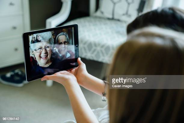 sisters video conferencing with grandparents through tablet computer at home - grandmother stock pictures, royalty-free photos & images