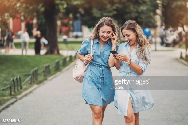 Sisters walking and listening from a smart phone