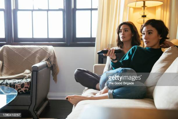 sisters watching tv on sofa at home - television stock pictures, royalty-free photos & images