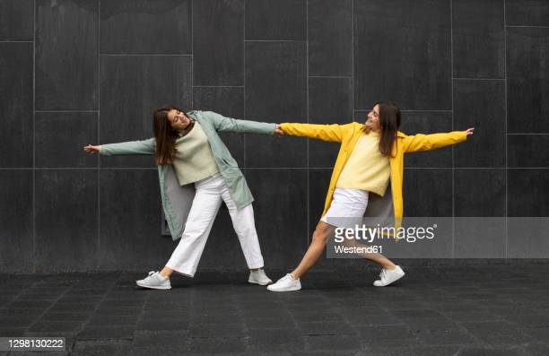 sisters wearing blue and yellow raincoats holding hands while dancing on footpath - sister stock pictures, royalty-free photos & images