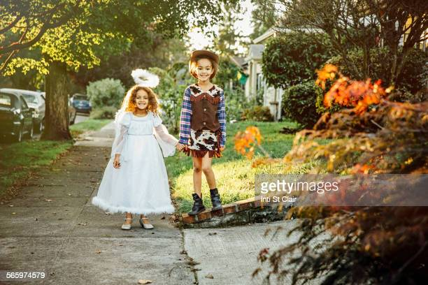 Sisters wearing Halloween costumes on sidewalk