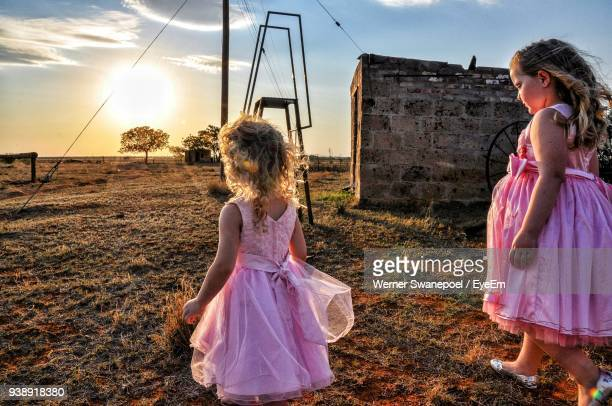 Sisters Wearing Pink Dress While Walking On Field During Sunset