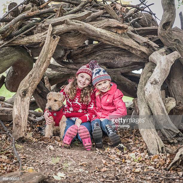 Sisters wearing wooly hats in their outdoor den with dog