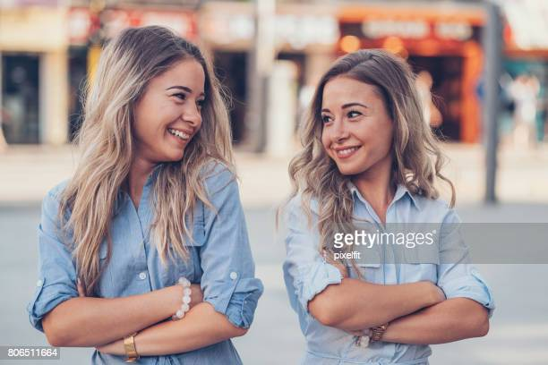 sisters with arms crossed looking at each other - twin stock pictures, royalty-free photos & images