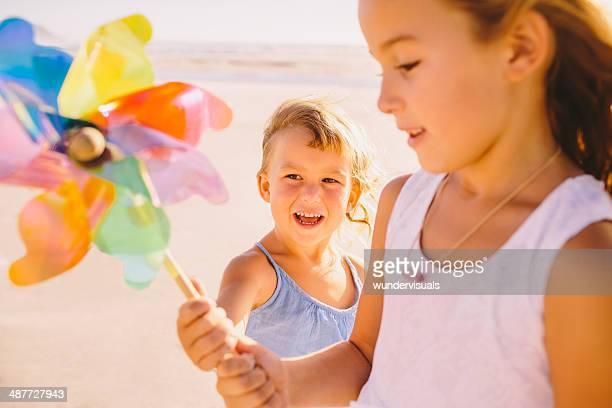 Sisters with pinwheel at beach