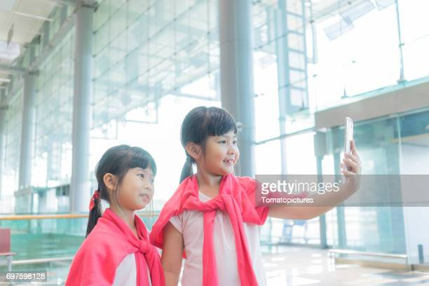 sisters with suitcase in airport - asian twins stock photos and pictures