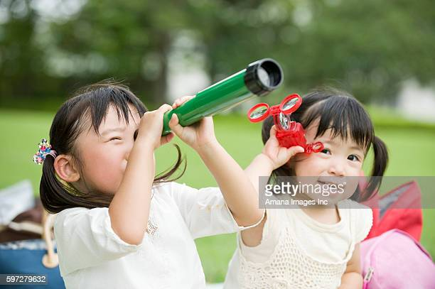 Sisters with telescope and binoculars