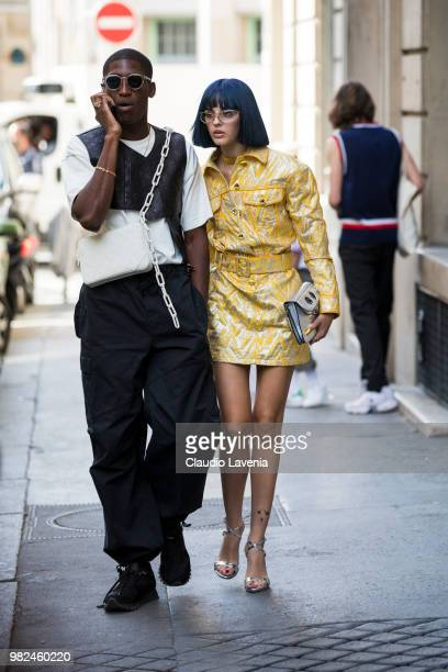 Sita Abellan wearing Moschino golden dress and JW Anderson bag and a guest wearing black and white t shirt and Louis Vuitton white bag are seen in...