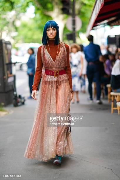 Sita Abellan wears an orange wool turtleneck pullover, a pink glitter pleated dress, a red Dior belt, a Dior bag, outside Dior, during Paris Fashion...